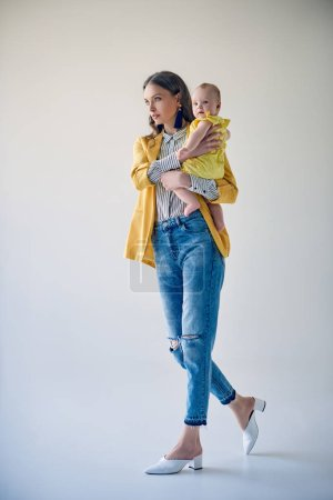 full length view of stylish young mother carrying adorable baby daughter and walking on grey
