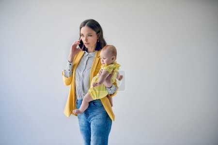 beautiful stylish mother carrying adorable infant daughter and talking by smartphone isolated on grey