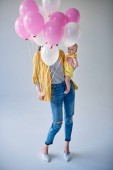 full length view of stylish woman carrying adorable baby girl and holding balloons on grey