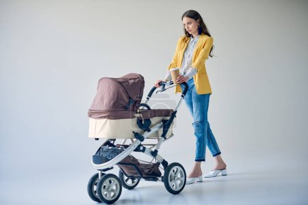 attractive fashionable woman holding disposable coffee cup and walking with baby carriage on grey