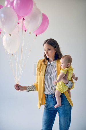 attractive stylish woman carrying adorable baby girl and holding bunch of balloons isolated on grey