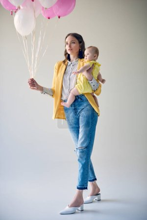 low angle view of stylish woman carrying adorable baby girl and holding bunch of balloons on grey