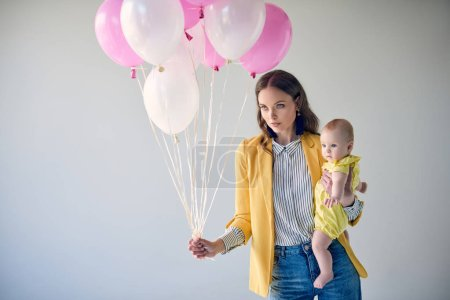stylish woman carrying adorable baby girl and holding bunch of balloons isolated on grey