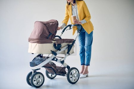 Foto de Tiro corto de moda mujer sosteniendo la taza de café desechables y pie con carro de bebé en gris - Imagen libre de derechos