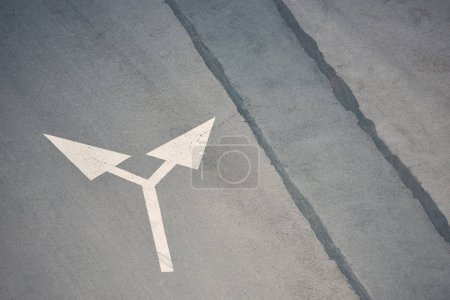 Photo for Two way arrow symbol on grey asphalt road - Royalty Free Image