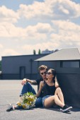 multicultural couple sitting on asphalt with bouquet of flowers