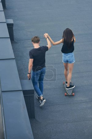 back view of man holding hands with girlfriend and teaching to ride on skateboard