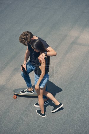 young couple hugging and skateboarding on longboard