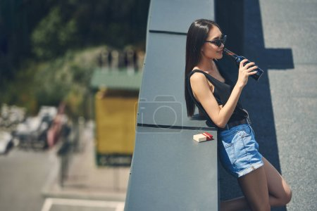 asian girl drinking beer on roof with cigarette pack