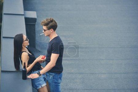 Foto de Sexy interracial pareja con cigarrillos y cerveza pasando tiempo juntos en el techo - Imagen libre de derechos