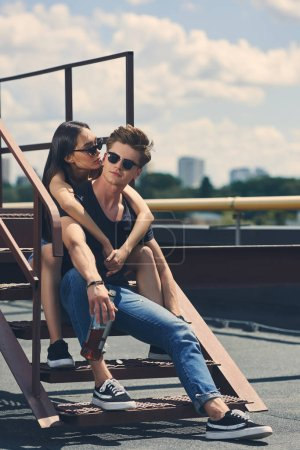 young multiethnic couple with bottle of whiskey sitting on stairs on roof