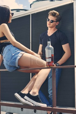 multicultural couple spending time together on roof with bottle of alcohol drink