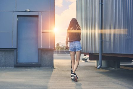 back view of young woman riding scooter on roof with sunbeams