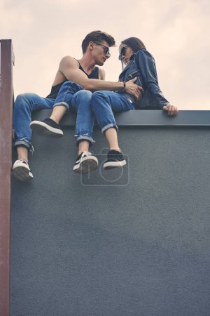 bottom view of stylish interracial couple flirting and hugging on roof