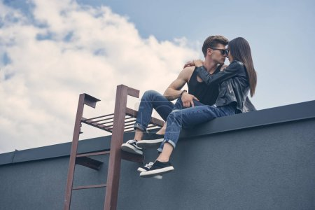 bottom view of beautiful interracial couple going to kiss while sitting on roof