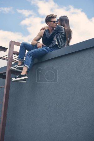 Photo pour Vue du bas de couple multiethnique sexy élégant va embrasser tout en étant assis sur le toit - image libre de droit