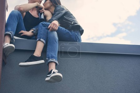 stylish multiethnic couple with bottle of beer embracing and sitting on roof