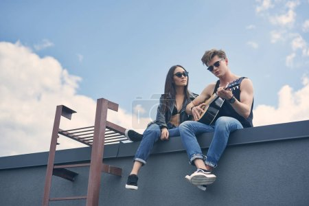 handsome boyfriend playing on acoustic guitar for his asian girlfriend on roof