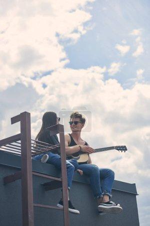 Photo pour Homme qui joue à la guitare acoustique pour sa copine asiatique sur toit - image libre de droit