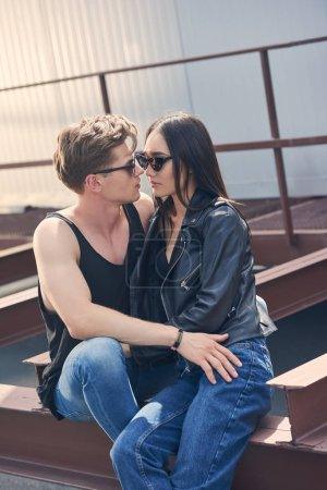 multicultural hot couple in sunglasses hugging on urban roof