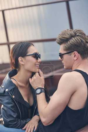 interracial happy couple in sunglasses flirting and looking at each other, man touching chin of girlfriend