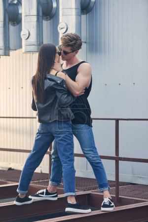 multicultural hot couple going to kiss while standing on urban roof