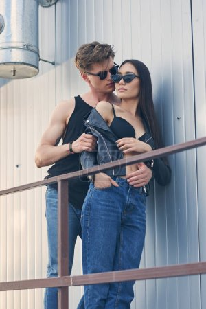 multiethnic stylish hot couple in sunglasses hugging on urban roof