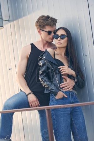 Photo for Multiethnic young hot couple in sunglasses embracing on urban roof - Royalty Free Image