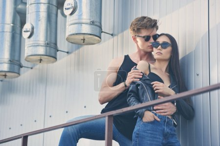 multiethnic hot couple in sunglasses hugging on urban roof