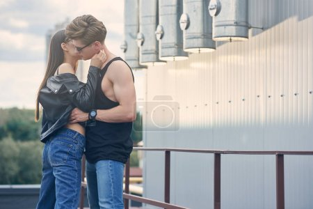 multicultural hot couple flirting and kissing on urban roof