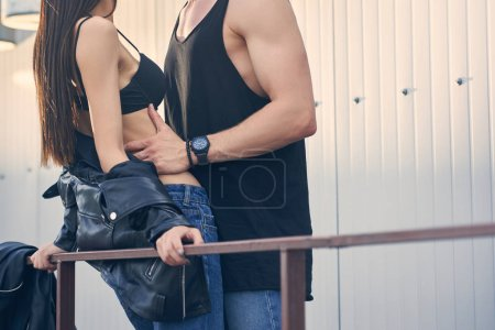cropped view of hot couple hugging on urban roof