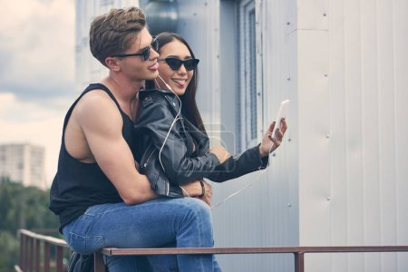 smiling multicultural couple listening music with earphones and taking selfie on smartphone