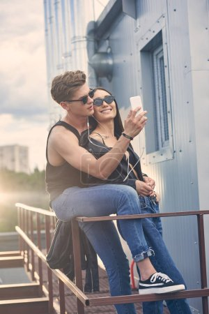 Photo for Happy interracial couple listening music with earphones and taking selfie on smartphone on roof - Royalty Free Image