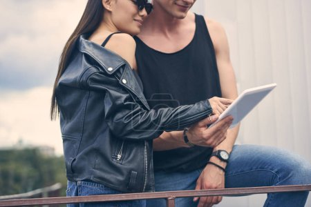 cropped view of young couple using digital device together