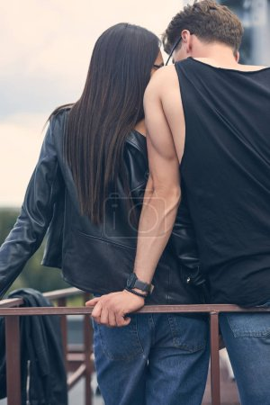 back view of stylish couple embracing near railings on roof