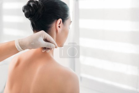 cropped shot of cosmetologist putting needles on womans body during acupuncture therapy in spa salon