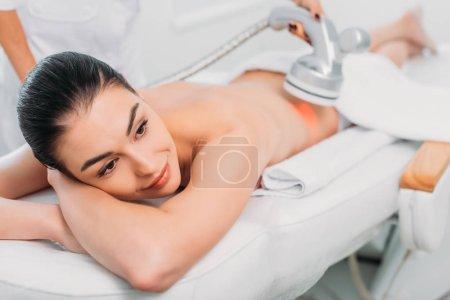Photo pour Belle femme souriante sur table de massage se faire masser électrique fait par un cosmétologue dans un salon de spa - image libre de droit
