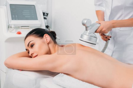 attractive woman on massage table getting electrical massage done by cosmetologist in spa salon