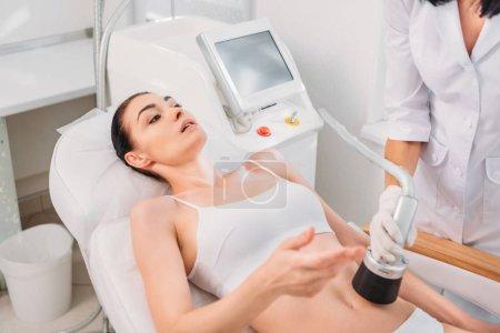 Photo pour Attrayant femme obtenir massage électrique fait par le cosmétologue dans le salon de spa - image libre de droit