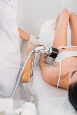 partial view of cosmetologist making electric massage to woman in white underwear at spa salon