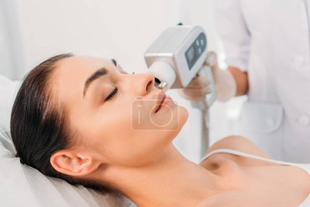 partial view of beautiful woman getting facial stimulating electrical massage made by cosmetologist in spa salon