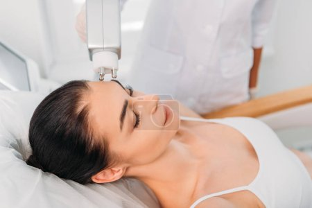 partial view of woman getting facial stimulating electrical massage made by cosmetologist in spa salon
