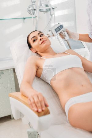 partial view of smiling woman in underwear getting facial stimulating electrical massage made by cosmetologist in spa salon