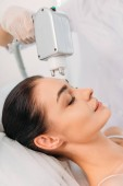 partial view of woman getting facial microcurrent therapy made by cosmetologist in spa salon