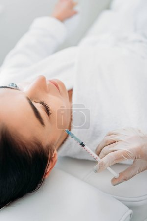 cropped shot of cosmetologist in latex glove with syringe making beauty injection to beautiful woman in spa salon