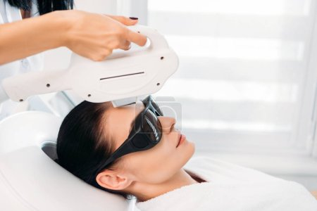woman in protective eyeglasses getting laser hair removal made by cosmetologist in spa salon