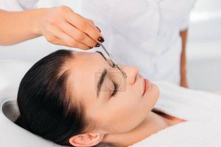 Beautiful woman receiving facial cleansing in spa center