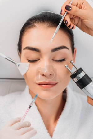 Photo for Overhead view of woman with various facial treatment equipment around in spa center - Royalty Free Image