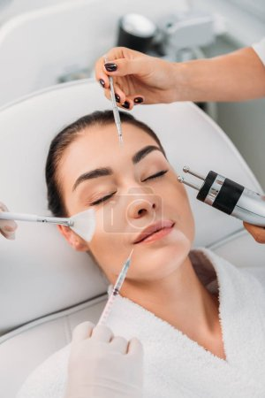 woman with various facial treatment equipment around in spa center
