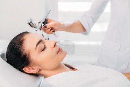 attractive woman receiving facial treatment in spa center
